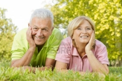 portrait-of-happy-old-people-lying-on-green-grass